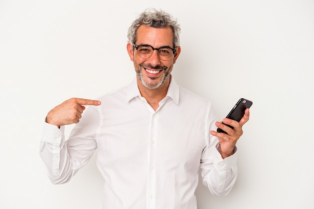 Middle age caucasian business man holding a mobile phone isolated on white background  person pointing by hand to a shirt copy space, proud and confident