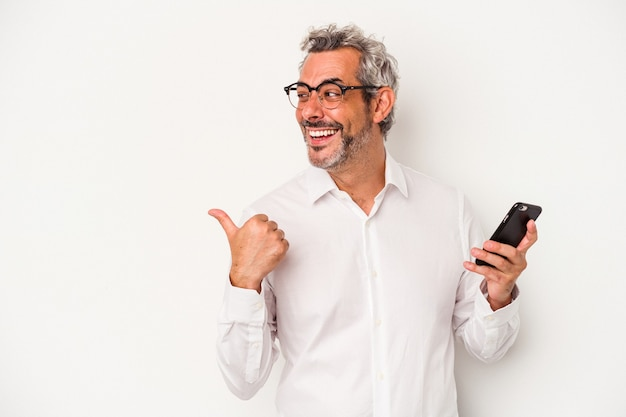 Middle age caucasian business man holding a mobile phone isolated on white background  points with thumb finger away, laughing and carefree.