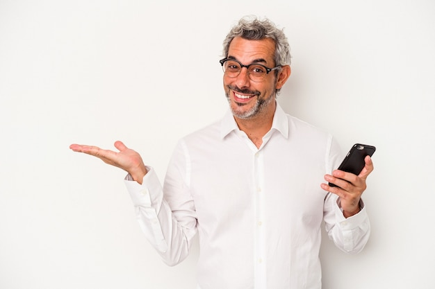 Middle age caucasian business man holding a mobile phone isolated on white background  showing a copy space on a palm and holding another hand on waist.