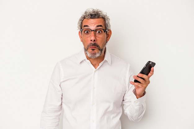 Middle age caucasian business man holding a mobile phone isolated on white background  shrugs shoulders and open eyes confused.