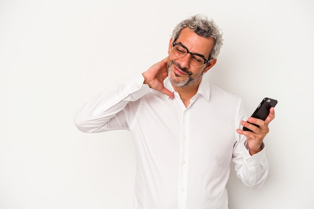 Middle age caucasian business man holding a mobile phone isolated on white background  touching back of head, thinking and making a choice.