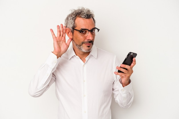 Middle age caucasian business man holding a mobile phone isolated on white background  trying to listening a gossip.