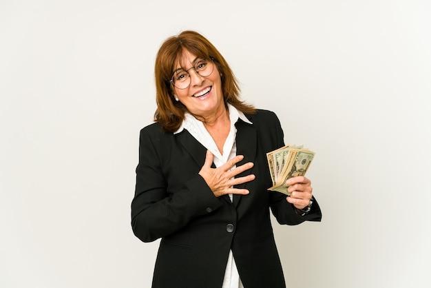 孤立した紙幣を持っている中年の白人ビジネスウーマンは、胸に手を置いて大声で笑います。