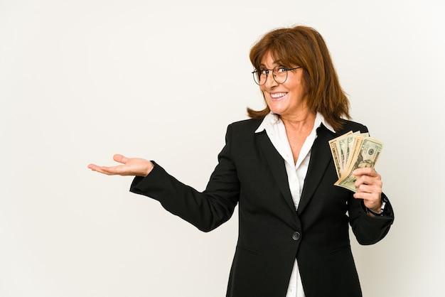 손바닥에 복사본 공간을 표시 하 고 허리에 다른 손을 잡고 절연 지폐를 들고 중 년 백인 비즈니스 여자.