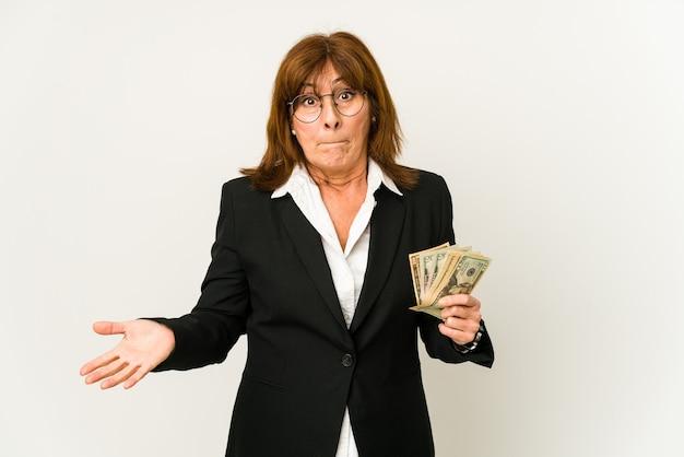 지폐를 들고 중년 백인 비즈니스 여자 어깨를 으쓱 어깨를 으쓱하고 눈을 뜨고 혼란스러워.