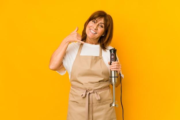 指で携帯電話の呼び出しジェスチャーを示す分離されたミキサーを保持している中年の白人料理人の女性。