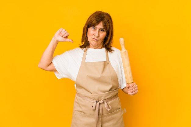 孤立したローラーを持っている中年の白人料理人の女性は、誇りと自信を持っています。