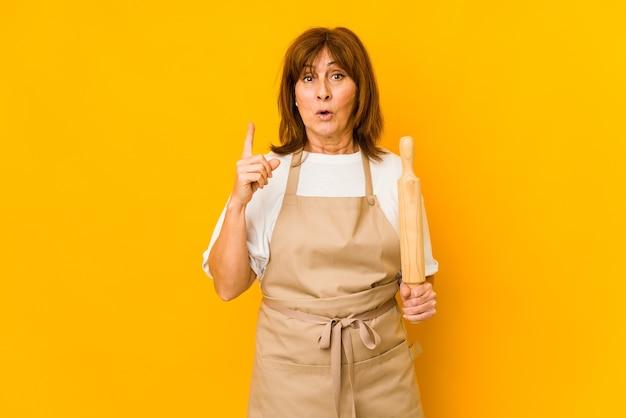 いくつかの素晴らしいアイデア、創造性の概念を持って孤立したローラーを保持している中年の白人料理人の女性。