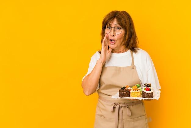 中年の白人料理人の女性が秘密の最新ニュースを言って脇を見ている