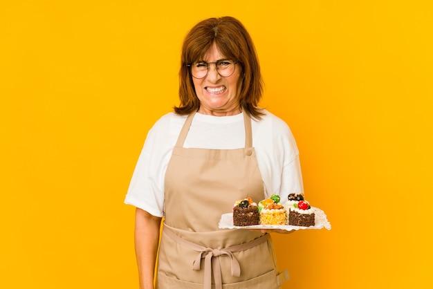 非常に怒って攻撃的に叫んでいる中年の白人料理人の女性。