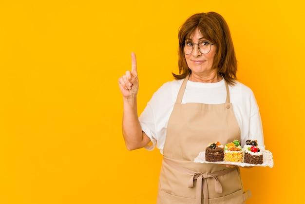 指でナンバーワンを示す中年白人料理人女性。