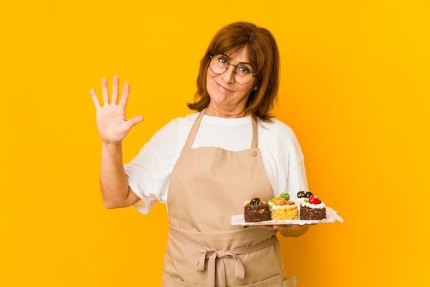 指で5番を見せて元気に笑っている中年白人料理人女性。