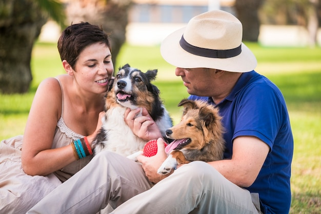 Middle age caucasian couple in outdoor leisure activity with best friends dogs all together having fun and love like an alternative family. happiness and enjoy lifestyle for cheerful people and animal