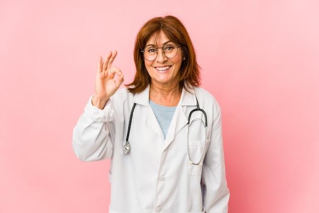 Женщина доктора среднего возраста кавказская изолировала жизнерадостную и уверенно показывая одобренный жест.