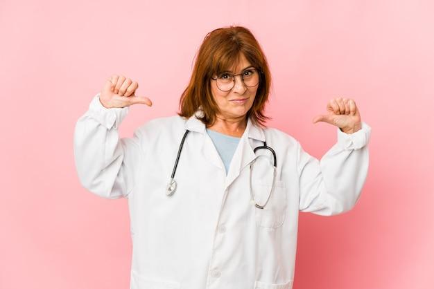 Изолированная женщина-врач среднего возраста кавказская чувствует себя гордой и уверенной в себе, примером для подражания.