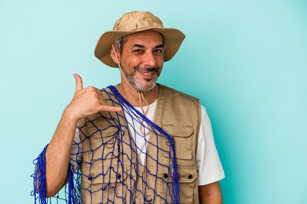 Middle age caucasian fisherman holding net isolated on blue background  showing a mobile phone call gesture with fingers.