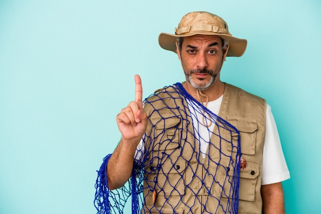 Middle age caucasian fisherman holding net isolated on blue background  showing number one with finger.