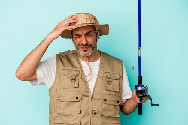 Middle age caucasian fisherman holding rod isolated on blue background  being shocked, she has remembered important meeting.