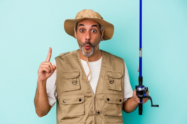 Middle age caucasian fisherman holding rod isolated on blue background  having some great idea, concept of creativity.