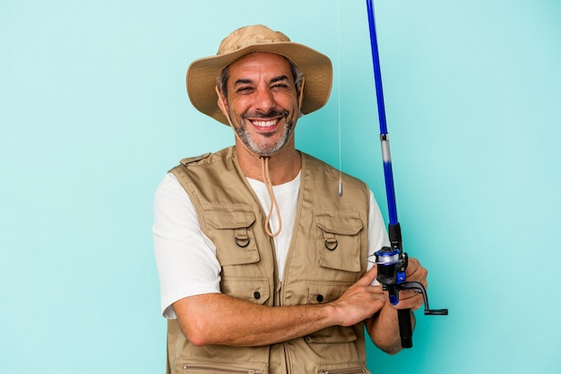 Middle age caucasian fisherman holding rod isolated on blue background  laughing and having fun.
