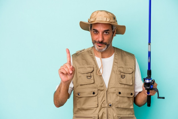Middle age caucasian fisherman holding rod isolated on blue background  showing number one with finger.