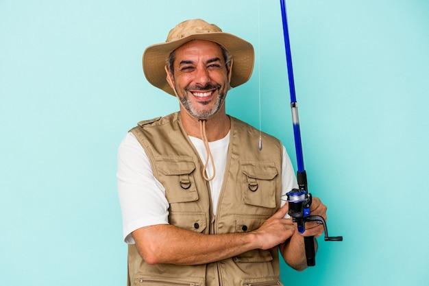 Кавказский рыбак среднего возраста, держащий стержень, изолированный на синем фоне, смеясь и весело.