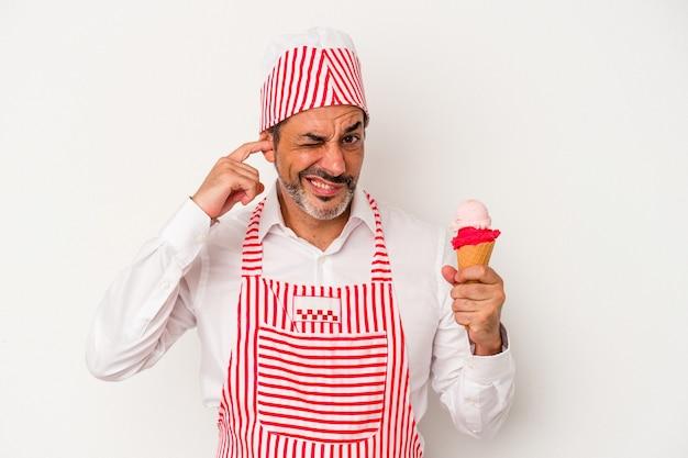 手で耳を覆う白い背景で隔離のアイスクリームを保持している中年白人製氷機白人男性。