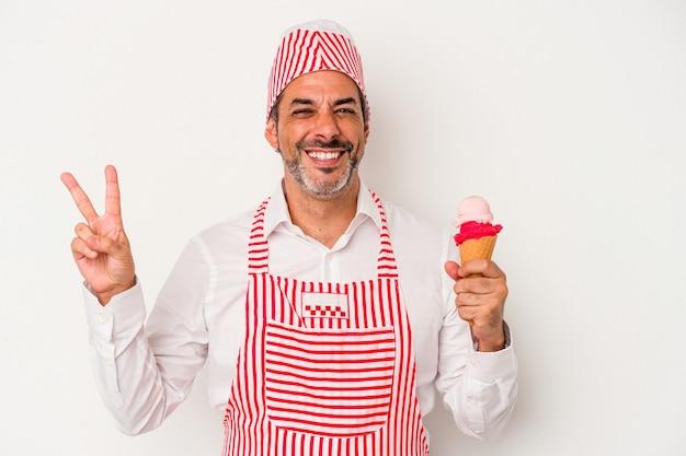 中年の白人製氷機白い背景に分離されたアイスクリームを持っている白人男性は、指で平和のシンボルを示して楽しくてのんきです。