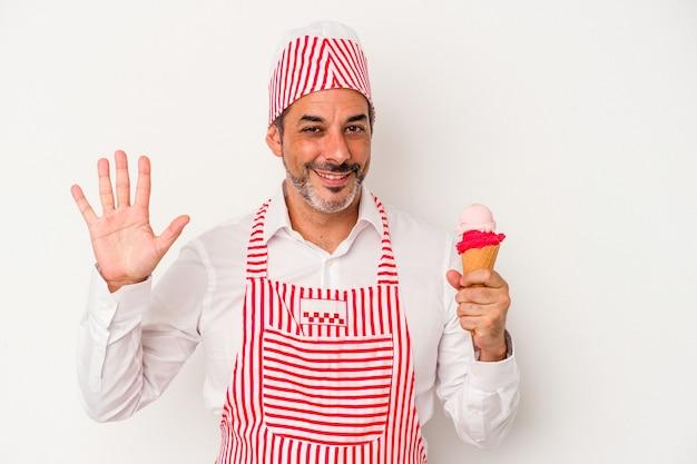 中年の白人製氷機白人男性が白い背景で隔離のアイスクリームを持って陽気な笑顔で5番を指で示しています。
