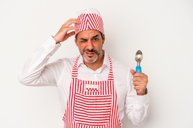 Middle age caucasian ice maker caucasian man holding a spoon isolated on white background  being shocked, she has remembered important meeting.