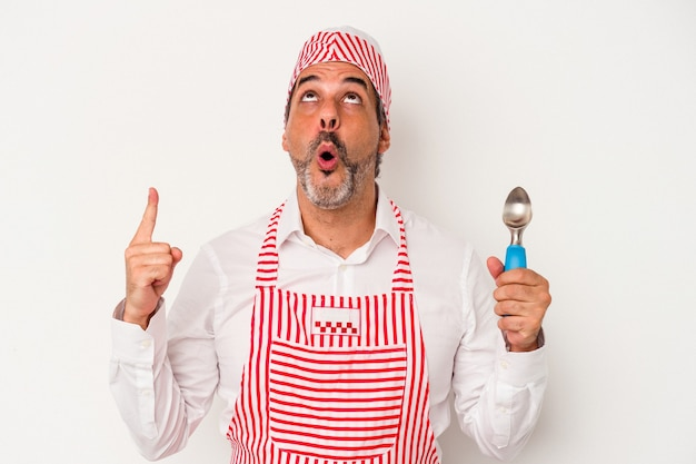 Middle age caucasian ice maker caucasian man holding a spoon isolated on white background  pointing upside with opened mouth.