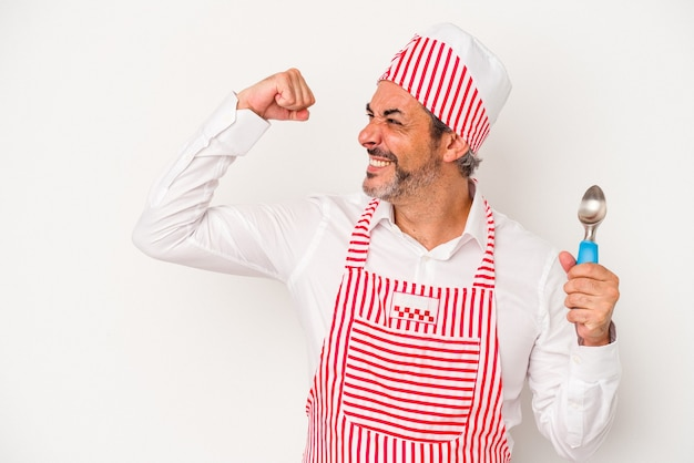 Middle age caucasian ice maker caucasian man holding a spoon isolated on white background  raising fist after a victory, winner concept.