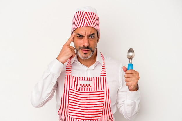 Middle age caucasian ice maker caucasian man holding a spoon isolated on white background  showing a disappointment gesture with forefinger.