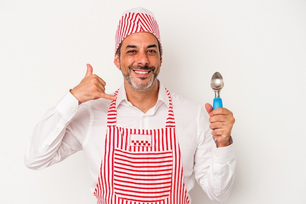 Middle age caucasian ice maker caucasian man holding a spoon isolated on white background  showing a mobile phone call gesture with fingers.