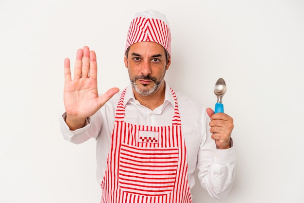 Middle age caucasian ice maker caucasian man holding a spoon isolated on white background  standing with outstretched hand showing stop sign, preventing you.