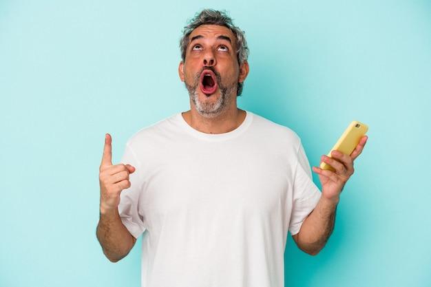 口を開けて逆さまを指している青い背景で隔離の携帯電話を保持している中年の白人男性。