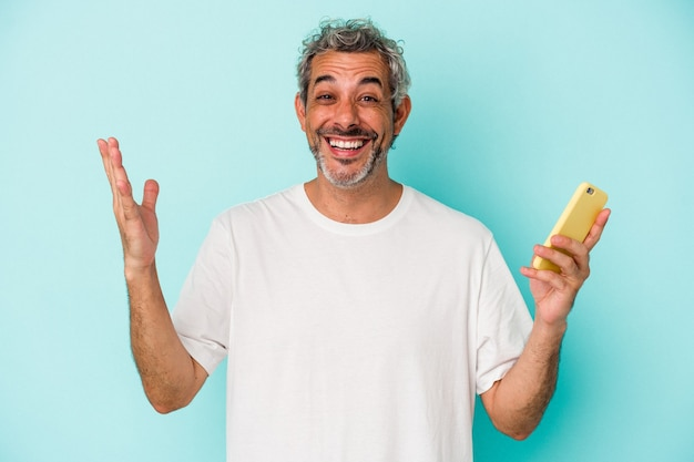 青い背景で隔離の携帯電話を持っている中年の白人男性は、嬉しい驚きを受け取り、興奮し、手を上げます。