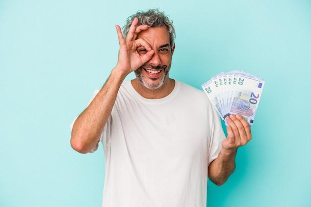 파란색 배경에 격리된 지폐를 들고 있는 중년 백인 남자는 눈에 확인 제스처를 유지하는 데 흥분했습니다.