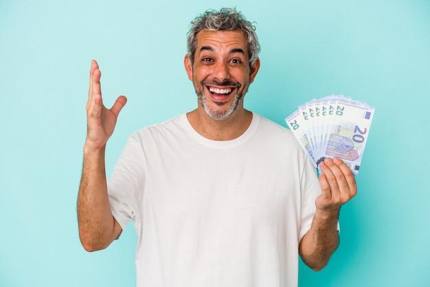푸른 배경에 격리된 지폐를 들고 있는 중년 백인 남자는 즐거운 놀라움과 흥분과 손을 들고 있습니다.
