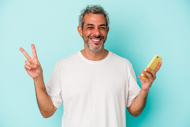 Middle age caucasian man holding a mobile phone isolated on blue background  joyful and carefree showing a peace symbol with fingers.
