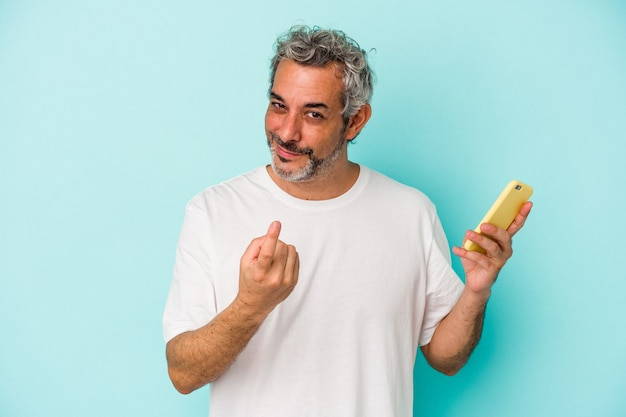 Middle age caucasian man holding a mobile phone isolated on blue background  pointing with finger at you as if inviting come closer.