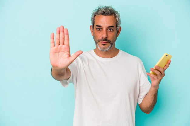 Middle age caucasian man holding a mobile phone isolated on blue background  standing with outstretched hand showing stop sign, preventing you.