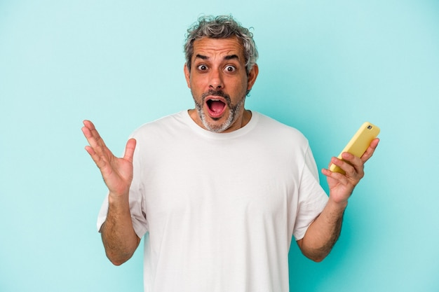 Middle age caucasian man holding a mobile phone isolated on blue background  surprised and shocked.