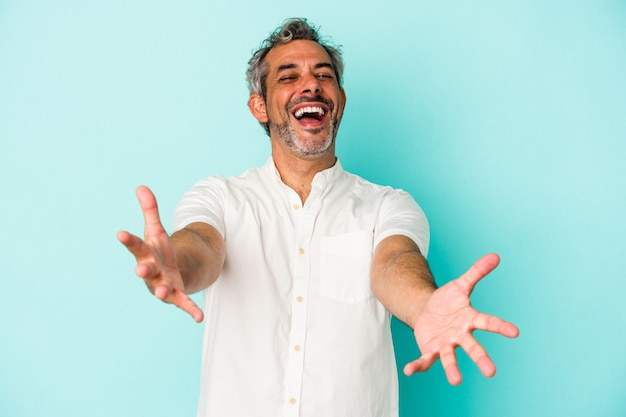 Middle age caucasian man isolated on blue background  feels confident giving a hug to the camera.