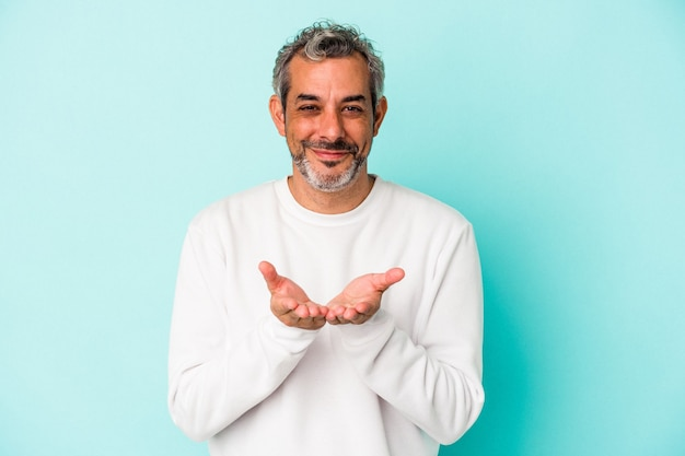 Middle age caucasian man isolated on blue background  holding something with palms, offering to camera.