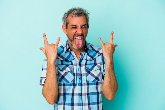 Middle age caucasian man isolated on blue background  showing a horns gesture as a revolution concept.