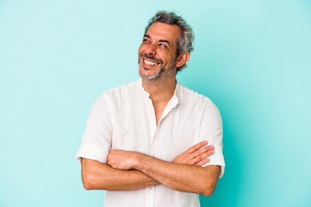 Middle age caucasian man isolated on blue background  smiling confident with crossed arms.