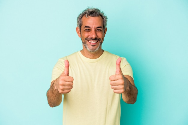 Middle age caucasian man isolated on blue background  smiling and raising thumb up