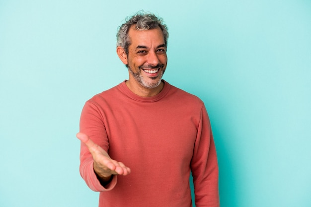 Middle age caucasian man isolated on blue background  stretching hand at camera in greeting gesture.