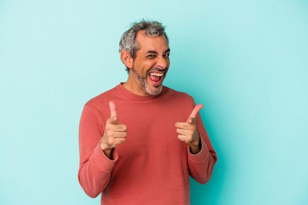 青い背景に孤立した中年の白人男性は、正面を指している陽気な笑顔。